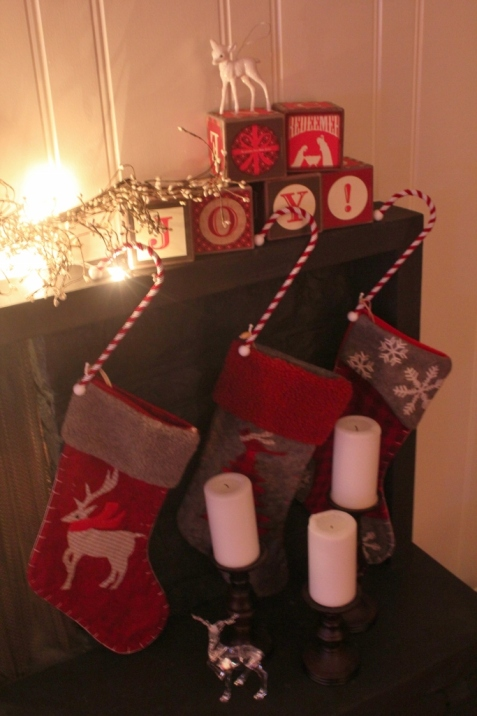 Redeemed Christmas blocks from Dayspring, stocking hangers from Target, dollar store deer, candle pedestals from thrift store and stockings are 3 years old from Superstore.